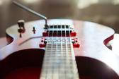 Guitarra eléctrica roja tendida en un terciopelo rojo. — Foto de Stock