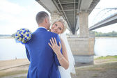 Bride and groom under a bridge — Stock Photo