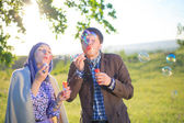 Charming couple blowing bubbles — Stock Photo