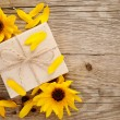 Ornamental sunflowers and gift box on wooden background — Stock Photo
