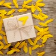 Stock Photo: Sunflower petals and gift box on wooden background