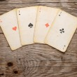 Old playing cards on wooden background — Stock Photo