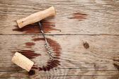 Corkscrew, cork and wine stains on wooden background — Stock Photo