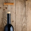 Bottle of wine with corkscrew on wooden background — Stock Photo #13745264