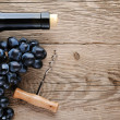 Bottle of wine, corkscrew and grape on wooden background — Stock Photo #13745317