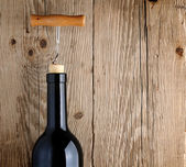 Bottle of wine with corkscrew on wooden background — Foto de Stock