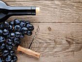 Bottle of wine, corkscrew and grape on wooden background — Stock Photo
