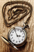 Vintage pocket watch on chain on wooden background — Stock Photo