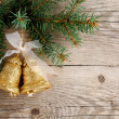 Golden bells with bow on christmas tree - Stock Photo