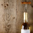 Wine bottle with corkscrew on wooden background — Stock Photo #18391211
