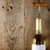 Wine bottle with corkscrew on wooden background — Stock Photo