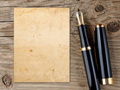 Fountain pen and vintage paper on old wooden background — Stock Photo