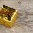 Golden gift box on wooden background — Stock Photo