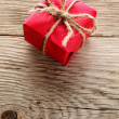 Gift box wrapped in red paper on wooden background — Stock Photo