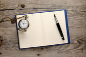 Antique watch and fountain pen on old notebook — Stock Photo