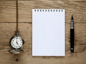 Pocket watch, fountain pen and note book on old wooden background — Stock Photo