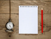 Pocket watch, pencil and note book on old wooden background — Stock Photo