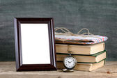 Photo frame and pile of old books on wooden table — Stock Photo