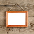 Photo frame hanging on old wooden wall — Stock Photo