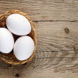 White eggs in basket on wooden background — Stock Photo