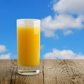 Glass of orange juice on wooden table on blue sky background — Stock Photo