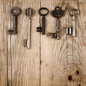 Vintage keys on old wooden background — Stock Photo