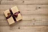 Vintage gift box with bow on wooden background — Stock Photo