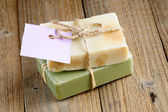 Two natural soap bars with tag on wooden background — Stock Photo