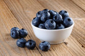 Blueberries in bowl on wooden background — Stock Photo