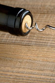 Wine bottle with corkscrew closeup on wooden background — Stock Photo