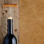 Láhev vína s vývrtkou na dřevěné pozadí — Stock fotografie