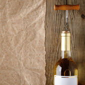Wine bottle with corkscrew on wood — Stock Photo