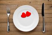 Twee rode harten op plaat op houten achtergrond — Stockfoto