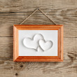 Two hearts in old picture frame hanging on wooden wall — Stock Photo #38655511
