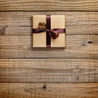Gift box with bow on wooden background — Stock Photo