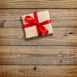 Gift box with red ribbon on wooden background — Stock Photo