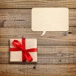 Gift box with red ribbon and speech bubble on wooden background — Stock Photo