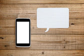 Smartphone with speech bubble on wooden background — Stock Photo