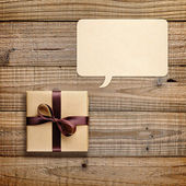 Gift box and speech bubble on wooden background — Stock Photo