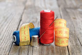 Spools of thread, needle, measuring tape and thimble on wooden table — Stock Photo