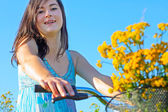 A pretty, young woman on a bike with yellow wildflowers — Стоковое фото