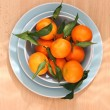 Ripe clementines on the blue, pastel plate — Stockfoto