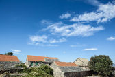 Old stone rustic house and blue sky — Stock Photo