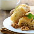 Traditional Turkish arabic dessert - baklava with honey and nuts - Stock Photo