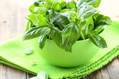 Fresh green basil on a wooden table — Stock Photo