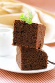 Chocolate cake brownie with a mint leaf on a plate — Stock Photo