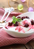 Dairy dessert with sweet sauce and cherries — Stock Photo