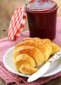 Croissant with jam on a plate - the French breakfast — Stock Photo