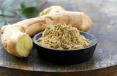 Ground ginger (spice) and fresh on a wooden board — Stock Photo