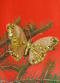 Christmas decoration (golden butterfly) on the branches of fir — Stockfoto